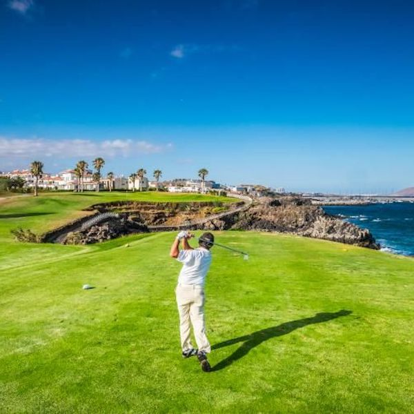 Golfer shoots for the green over water on Amarilla Golf, Tenerife