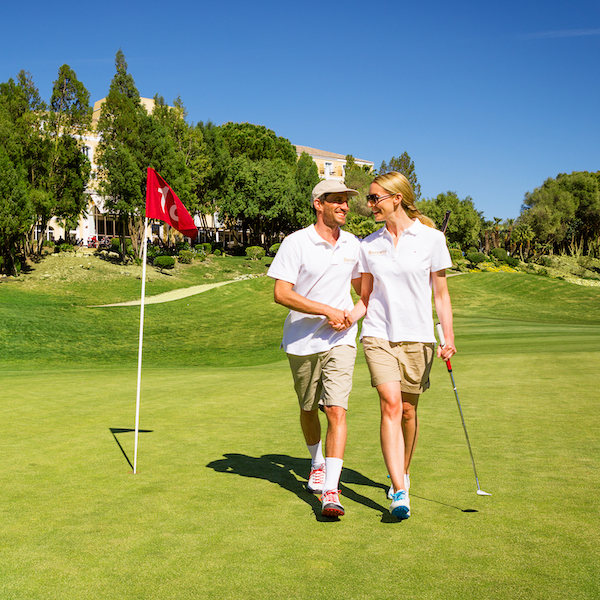 Couple leaving green at Montecastillo Golf, Costa de la Luz, Spain