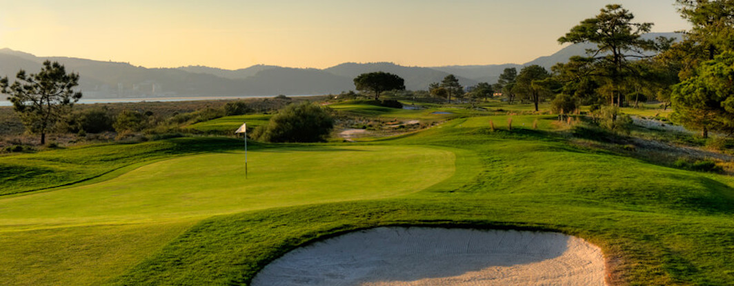 Troia Golf green guarded by bunker with view to the hills