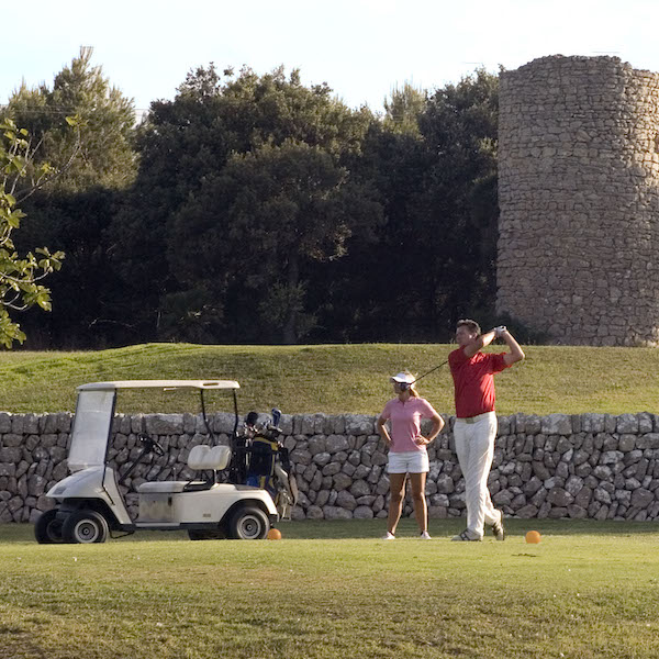 Couple golfing with a buggy at Capdepera Golf, Mallorca