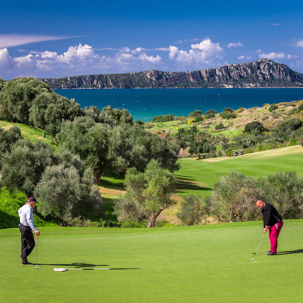 2 golfers putting on a green overlooking the Mediterranean on the Bay Course, Costa Navarino, Greece