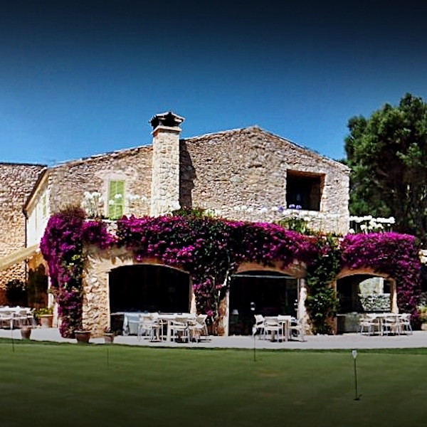 Historic Pula Golf Hotel surrounded by bougainvillea with putting green in foreground