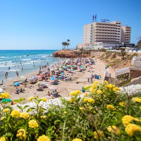 View from beach of La Zenia Hotel with flowers in the foreground